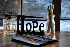 Approvisionnements de peintres autour d'un signe d'espoir Photographie stock