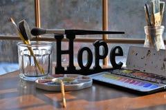 Approvisionnements de peintres autour d'un signe d'espoir Photos stock
