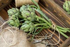 Approvisionnements et matériaux pour le bouquet d'artichaut sur le backgroun en bois images libres de droits