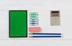 Approvisionnements organisés pour le travail ou l'école sur le bureau blanc Images libres de droits