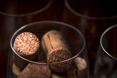 Approvvigionando, concetto del partito: immagine del primo piano del vetro di vino con i sugheri ed i vetri vuoti su un fondo di  Fotografia Stock