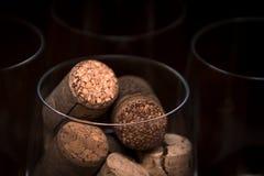 Approvvigionando, concetto del partito: immagine del primo piano del vetro di vino con i sugheri ed i vetri vuoti su un fondo di  Immagine Stock Libera da Diritti