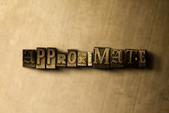 APPROXIMATE - close-up of grungy vintage typeset word on metal backdrop Stock Photography