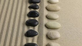 Approximation of black and white stones lying on flat and striped sand. Concept of relaxation stock footage