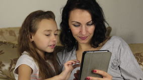 Approximation, zoom, daughter teaches mother to play the game on the tablet. stock video footage