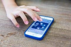 Apps scelti della mano femminile sul iPhone di Apple Immagini Stock Libere da Diritti