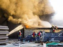 Appui de plusieurs sapeurs-pompiers à outre du feu d'usine images libres de droits