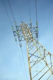 Appui vertical à haute tension en métal de ligne électrique au-dessus de ciel bleu sans nuages clair Photographie stock libre de droits