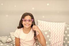 Appui verticaux de cabine de photo de soir?e pyjamas La pose gaie de fille d'enfant avec de r?tros lunettes roses font la f?te l' image libre de droits