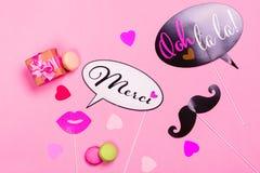 Appui verticaux français de photo de thème - lèvres, moustaches, boîte-cadeau et macarons sur le fond rose de jour de valentines Images stock