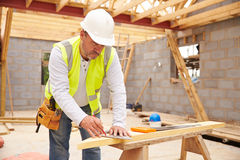 Appuis de Cutting House Roof de charpentier sur le chantier Photographie stock