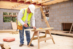 Appuis de Cutting House Roof de charpentier sur le chantier Photographie stock libre de droits