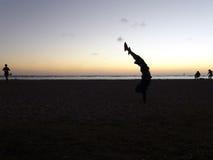 Appuis renversés d'homme sur la plage de Moana d'aile du nez au crépuscule Images stock