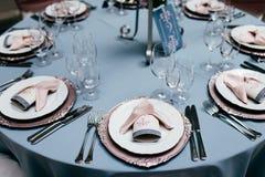 Appuntamenti della Tabella Presenti la regolazione con i piatti vuoti, forcelle, vetri e coltelli e tableclothes blu-chiaro Tavol fotografie stock