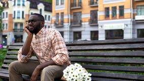 Appuntamento al buio, ragazza aspettante nervosa del giovane, banco di parco di seduta con i fiori fotografie stock libere da diritti