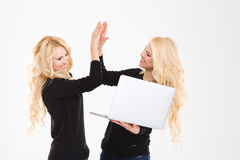 ?孪生与便携式计算机庆祝他们的成功的appy姐妹 库存照片