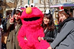 Appy azjatykcie dziewczyny biorą strzał z sesame street Elmo w universal studio Japonia USJ, Osaka, Japonia zdjęcia royalty free