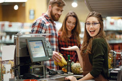 ?appy cashier woman on workspace in supermarket shop. Image of happy cashier women on workspace in supermarket shop. Looking at camera Royalty Free Stock Photo