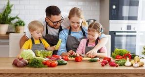 Appy familj med barnet som förbereder grönsaksallad Arkivbild