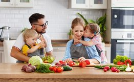 Appy family with child preparing vegetable salad. Happy family with child preparing vegetable salad at home royalty free stock image
