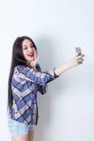 Appy flicka för Ð- som tar selfie med hennes smartphone Arkivfoton