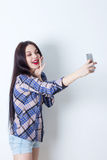 Нappy girl taking selfie with her smartphone Stock Photos