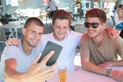 Appy male friends taking selfie and drinking beer at bar. Friends Stock Image