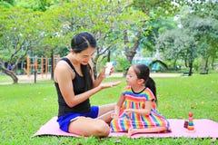 Appying λοσιόν σωμάτων μητέρων για της κόρης στο θερινό πάρκο στοκ εικόνες με δικαίωμα ελεύθερης χρήσης