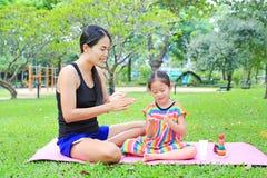 Appying λοσιόν σωμάτων μητέρων για της κόρης στο θερινό πάρκο στοκ εικόνα με δικαίωμα ελεύθερης χρήσης