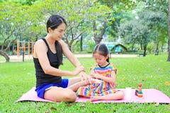 Appying λοσιόν σωμάτων μητέρων για της κόρης στο θερινό πάρκο στοκ φωτογραφίες με δικαίωμα ελεύθερης χρήσης