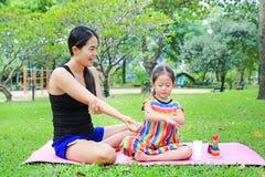 Appying λοσιόν σωμάτων μητέρων για της κόρης στο θερινό πάρκο στοκ εικόνα
