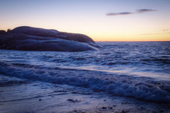 Après coucher du soleil avec des vagues sur des roches Images stock