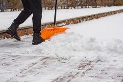 Après les chutes de neige, un homme dégage la neige de la route en hiver, travail pendant la saison d'hiver photographie stock libre de droits