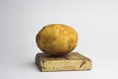 Après récupération des pommes de terre d'un plat blanc d'un plat en bois Photos stock