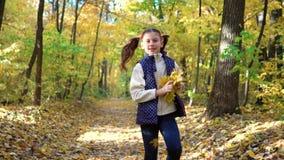Après tir de peu de fille courant dans le parc d'automne et des feuilles de lancement banque de vidéos