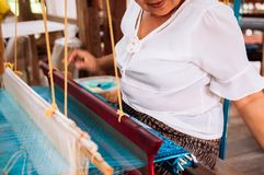 Asian Woman working on Vintage Laos style wooden weaving loom with silk fiber. APR 4, 2018 Luang Prabang, Laos - Laotian woman working on Vintage Laos style stock image