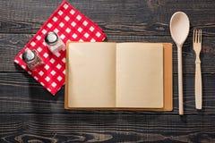 Apra gli agitatori di sale del libro di ricetta di sale bianco e di un pepperbox sulla a fotografie stock