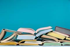 Apra i libri variopinti della libro con copertina rigida su fondo blu Di nuovo al banco Copi lo spazio per testo Concetto di affa Fotografie Stock