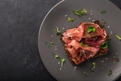 Apra i sanwiches con il pane di segale scuro, il prosciutto di Parma ed il gatto seccato al sole fotografia stock libera da diritti