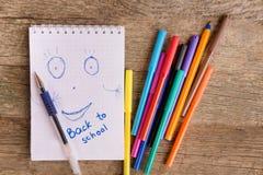 Apra il blocco note bianco con il disegno e l'iscrizione DI NUOVO ALLA SCUOLA con i pennarelli variopinti e le penne di palla sul Fotografia Stock