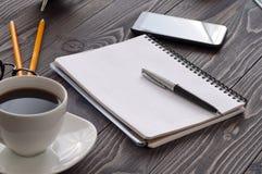 Apra il blocco note con le pagine in bianco, la penna e la tazza di caffè fotografia stock