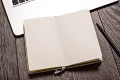 Apra il blocco note con le pagine in bianco sulla tavola con il computer portatile Fotografie Stock