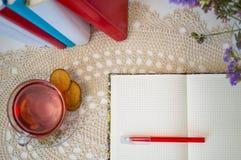 Apra il blocco note e la tazza in bianco di tè sulla tavola Fotografie Stock Libere da Diritti