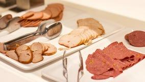 Apra il buffet all'hotel Varietà di prosciutto e di salsiccia sul pl bianco fotografie stock libere da diritti