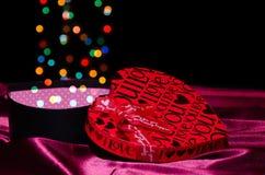 Apra il cuore a forma di scatola del regalo con Bokeh Fotografia Stock