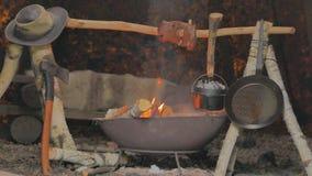Apra il fuoco che cucina, arrostendo la carne mentre cuociono il pane in un forno olandese video d archivio