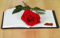 Apra il libro del giornale con una rosa rossa Fotografie Stock