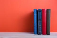 Apra il libro della libro con copertina rigida sulla tavola di legno della piattaforma e sul fondo rosso Fotografia Stock Libera da Diritti
