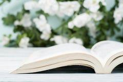 Apra il libro della libro con copertina rigida sulla tavola di legno e sullo sfondo naturale Di nuovo al banco Copi lo spazio per Fotografia Stock