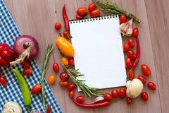Apra il libro di ricetta con gli ortaggi freschi e le erbe su di legno immagine stock